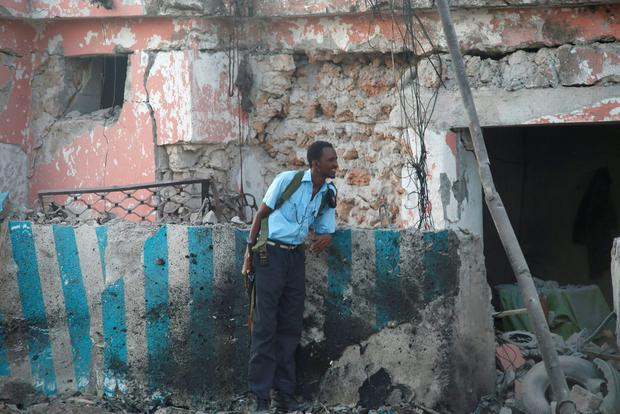 A Somali policeman holds his position during an exchange of fire with Islamist al Shabaab gunmen outside a hotel in Somalia's capital Mogadishu, November 1, 2015. Two bombs ripped into a hotel in the Somali capital on Sunday and security forces fought Islamist al Shabaab gunmen who stormed inside the building for hours afterwards, police and witnesses said. At least 11 people were killed. Al Shabaab, which has frequently launched attacks in Mogadishu in its bid to topple the Western-backed government, said it was behind the assault on the Sahafi hotel where government officials and lawmakers stay. REUTERS/Feisal Omar