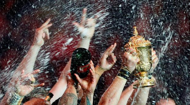 New Zealand's team celebrates with the Webb Ellis trophy after winning the Rugby World Cup Final against Australia