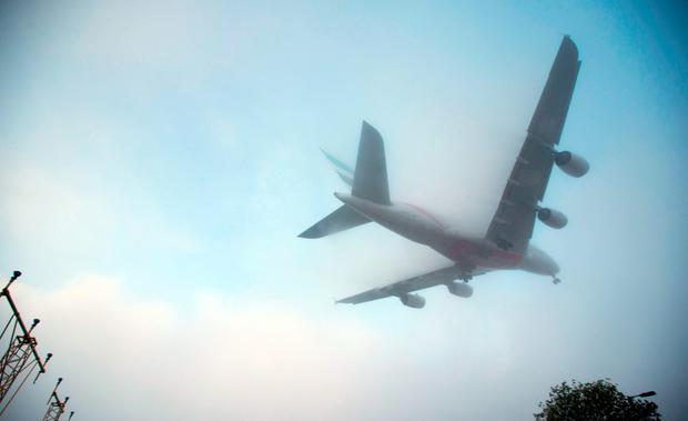 PA File photo - A plane lands in thick mist at Heathrow Airport in 2014. Photo: Steve Parsons/PA Wire