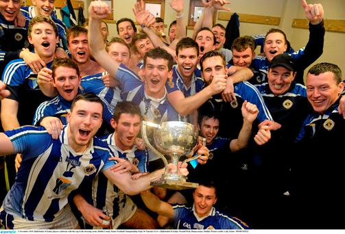 Ballyboden St Endas players celebrate with the cup in the dressing room.