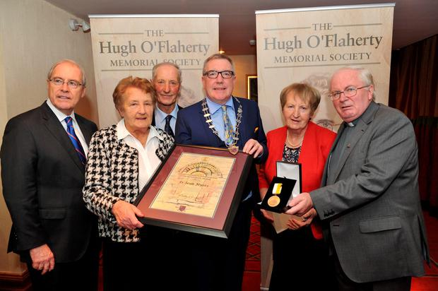 Kilkenny mayor Bobby O'Connell presents the award to Daniel Myers, Noreen Hayes and Teresa Cunningham, the family of Fr Seán Myers. Also present were US Ambassador to Ireland Kevin O'Malley (left) and Fr Dan Baragry (right).