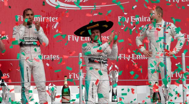 Mercedes Formula One driver Nico Rosberg (centre) of Germany celebrates between his teammate Lewis Hamilton (left) of Britain and Williams Formula One driver Valtteri Bottas of Finland after winning the Mexican F1 Grand Prix at Autodromo Hermanos Rodriguez in Mexico City