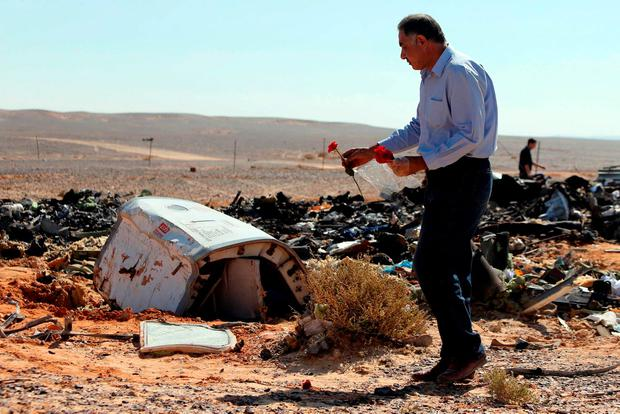 An Egyptian man puts flowers near debris at the crash site of a Russian airliner in al-Hasanah area at El Arish city, northern Egypt