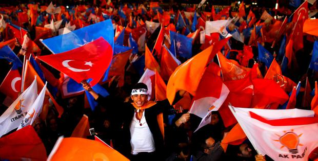 A young man waves flags outside the AK Party headquarters in Ankara