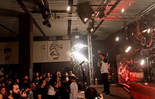 A member of the Romanian metal band 'Goodbye to Gravity' performs as fireworks erupt on the stage of a nightclub, before a fire broke out in Bucharest