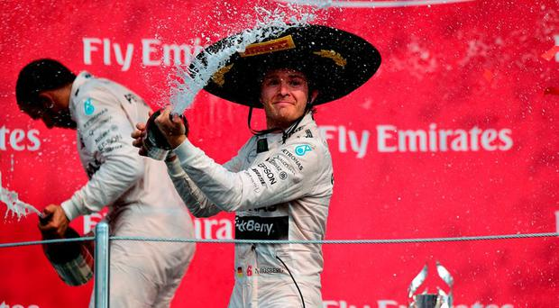 Nico Rosberg (R) celebrates his victory with teammate Lewis Hamilton on the podium after winning the Formula 1 Grand Prix race at the Autodromo Hermanos Rodriguez in Mexico City