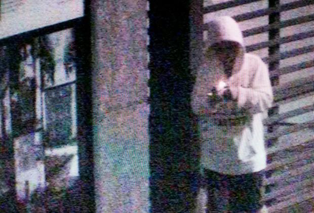 CCTV images show thug lighting and tossing a burning object