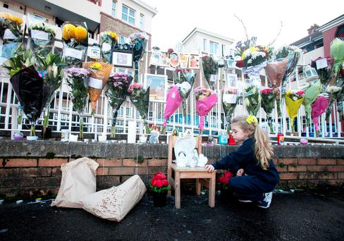 Cassie Dempsey (4) looks at flowers near the scene of the stabbing at the Oliver Bond flat complex. Photo: Gareth Chaney