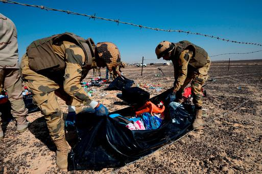 Egyptian soldiers collect personal belongings of plane crash victims at the crash site in the Sinai Peninsula. Photo: AP
