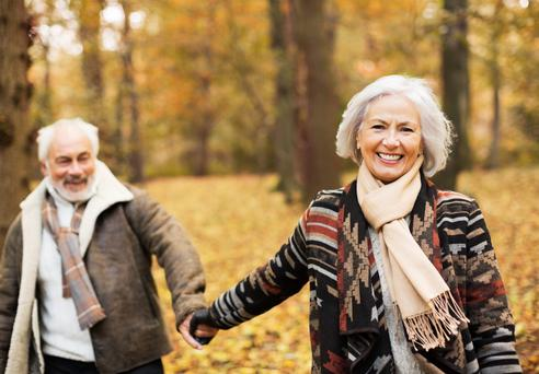 Older couple walking together in park