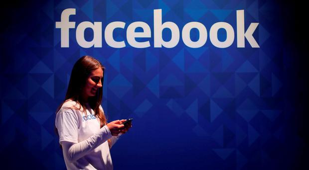 A woman uses her phone at the Facebook stand during the three day Web Summit: Niall Carson/PA Wire