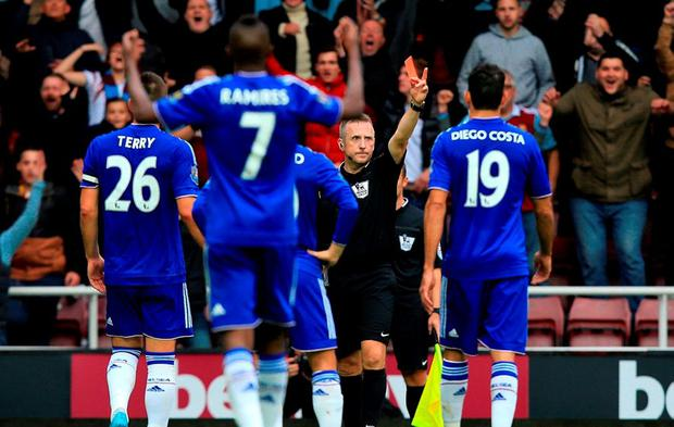 Referee Jonathan Moss shows a red card after Chelsea's Nemanja Matic picked up his second yellow card during the Barclays Premier League match at Upton Park when Jose Mourinho was later sent to the stand