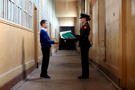 Ben Burns (10), from Our Lady of Lourdes National School, Inchicore, Dublin, is presented with the Irish flag and a copy of the Proclamation by Capt. Ciara Ní Ruairc as part of the Ireland 2016 Centenary Programme