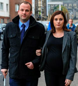 Eoin White, from Carrigaline, Co Cork, leaves court with his wife Sarah after he settled his action against the HSE. Photo: Courtpix