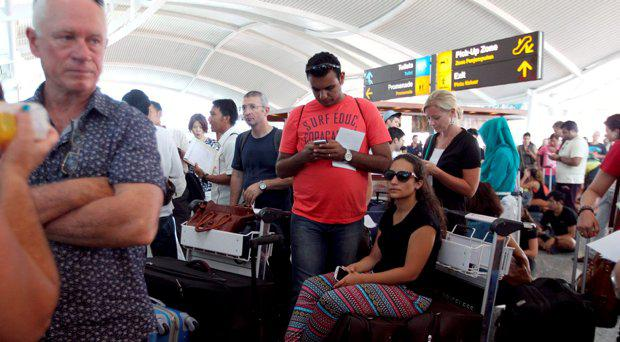 Passengers wait to check the status of their flights with airline desk at Ngurah Rai International Airport in Bali, Indonesia Wednesday, Nov. 4, 2015
