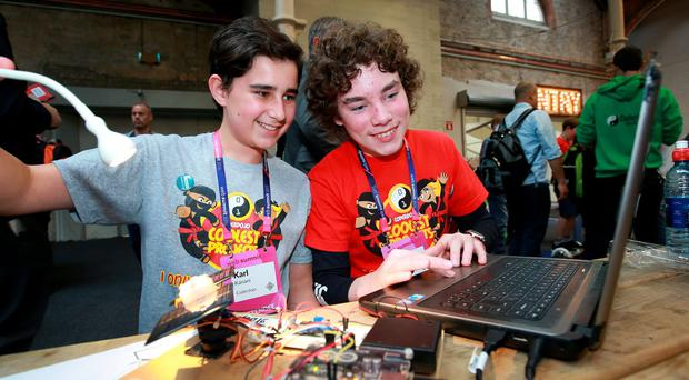Karl Kanani [13] and Leo Bourke [12] both from Dalkey try out their solar tracking panel [on left] which creates enouth power to cahrge the battery on the laptop on the CoderDojo stand at the Web Summit at the RDS. Pic Credit Frank Mc Grath