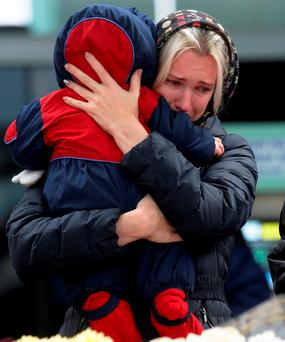 A woman with her baby reacts as she stands near to floral tributes for the victims of the plane crash, at Pulkovo airport outside St Petersburg, Russia.