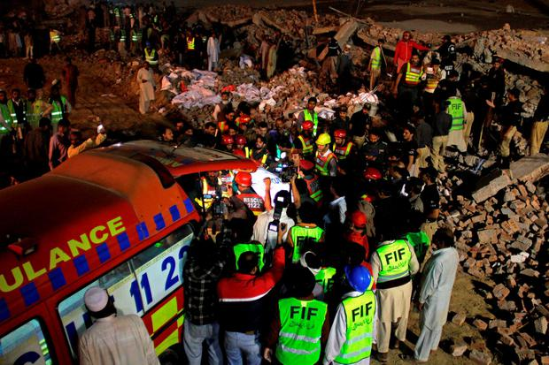 Pakistan rescue workers carry a victim to an ambulance at the site of a collapsed building in Lahore, Pakistan, Wednesday, Nov. 4, 2015. (AP Photo/K.M. Chaudary)