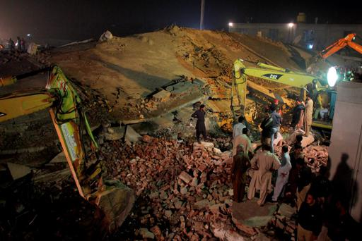 Pakistan rescue workers use heavy machinery to remove debris of a collapsed building in Lahore, Pakistan, Wednesday, Nov. 4, 2015. (AP Photo/K.M. Chaudary)