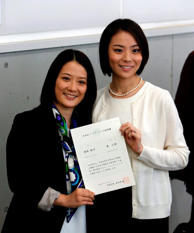 Hiroko Masuhara (L) and her partner Koyuki Higashi hold their partnership certificate as they pose for pictures outside the Shibuya ward office after the ward office issued the nation's first same sex partnership certificates in Tokyo, Japan, November 5, 2015. REUTERS/Yuya Shino