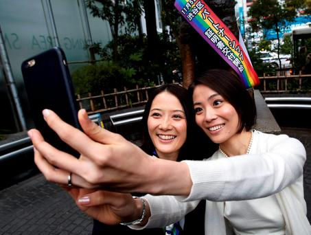Hiroko Masuhara (L) and her partner Koyuki Higashi take 'selfie' pictures in front of the statue of famous Japanese dog Hachiko after the ward office issued the nation's first same sex partnership certificates in Tokyo, Japan, November 5, 2015. REUTERS/Yuya Shino