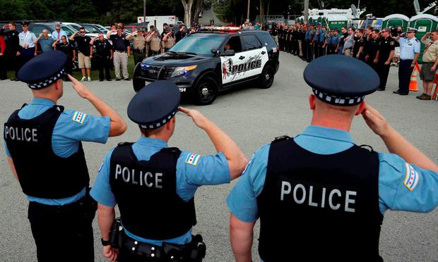 Police officers salute at a vigil for slain Fox Lake Police Lieutenant Charles Joseph Gliniewicz in Fox Lake, Illinois, United States in this September 2, 2015 file photo. REUTERS/Jim Young/Files