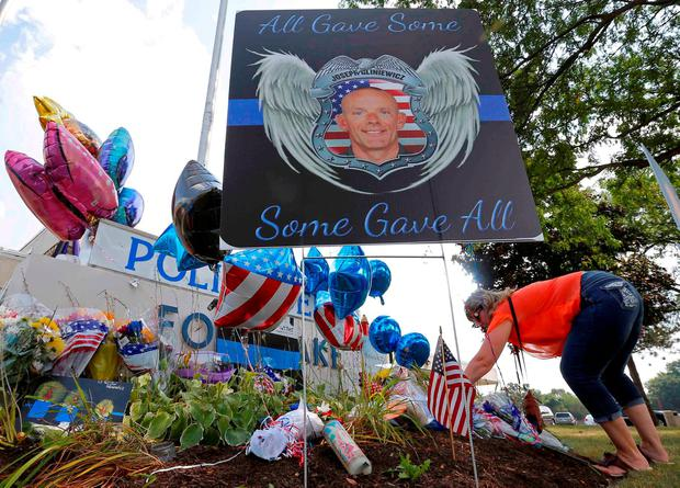 A woman lays flowers at a vigil for slain Fox Lake Police Lieutenant Charles Joseph Gliniewicz in Fox Lake, Illinois, United States in this September 2, 2015 file photo.REUTERS/Jim Young/Files