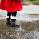 Child standing in a rain puddle