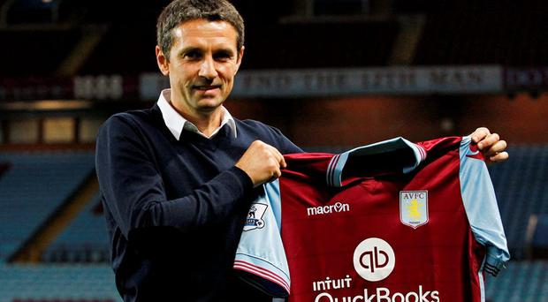 Aston Villa manager Remi Garde poses with the shirt after the press conference Action Images via Reuters / Craig Brough