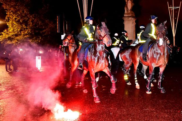 Police on horses outside Buckingham Palace in London, during the Million Mask March bonfire night protest organised by activist group Anonymous.