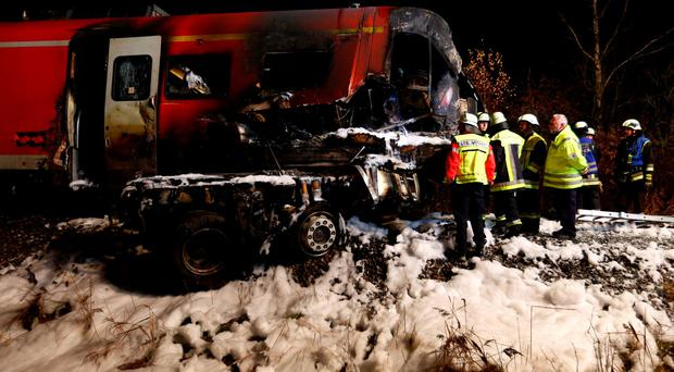 Firefighters look for the train driver of a regional passenger train that collided with a heavy-duty lorry at a railway crossing near the Bavarian village of Freihung, Germany, November 6, 2015. REUTERS/Michaela Rehle