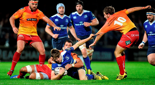 Garry Ringrose, Leinster, is tackled by Aaron Shingler and Dan Jones, Scarlets