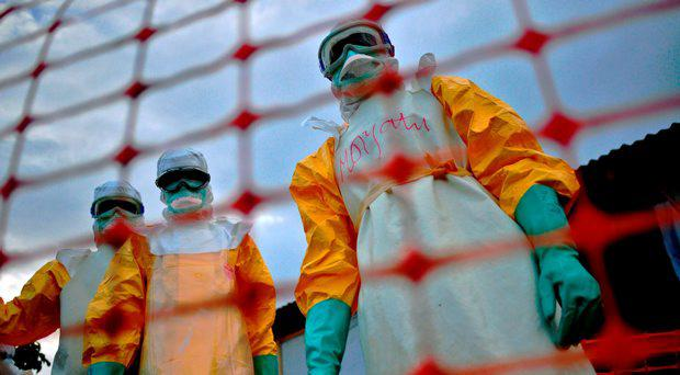 A file picture taken on August 14, 2014 shows Medecins Sans Frontieres (MSF) medical staff wearing protective clothing treating the body of an Ebola victim at their facility in Kailahun