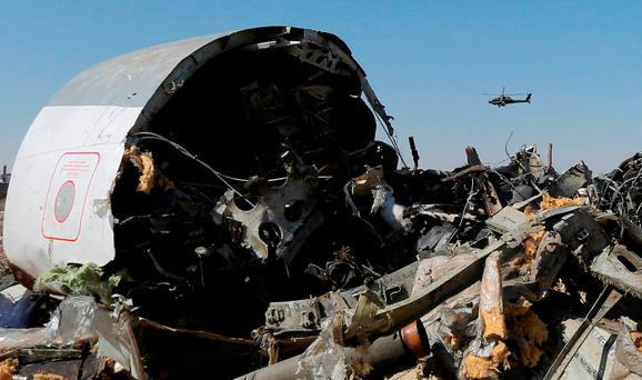An Egyptian military helicopter flies over debris from a Russian airliner which crashed at the Hassana area in Arish city, north Egypt, November 1, 2015