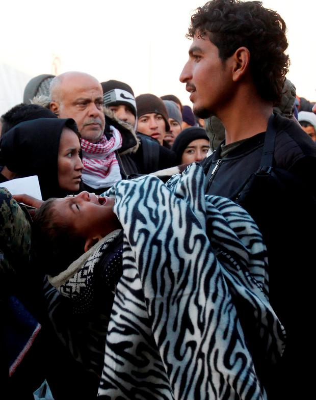 A child cries as people wait to board a train heading towards Serbia at the transit center for refugees near the southern Macedonian town of Gevgelija, after crossing the border from Greece, on Saturday, Nov. 7, 2015. (AP Photo/Boris Grdanoski)