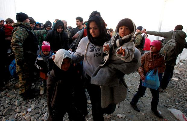 Police officers help families with children to board a train heading towards Serbia at the transit center for refugees near the southern Macedonian town of Gevgelija, on Saturday, Nov. 7, 2015. (AP Photo/Boris Grdanoski)