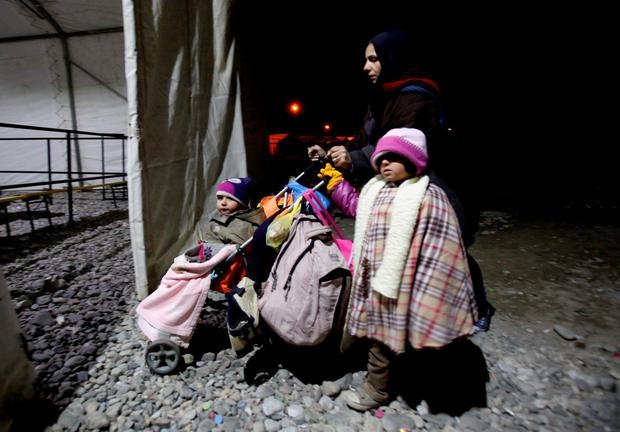 A woman and children arrive at the transit center for refugees near the southern Macedonian town of Gevgelija, after crossing the border from Greece, early Saturday, Nov. 7, 2015. (AP Photo/Boris Grdanoski)