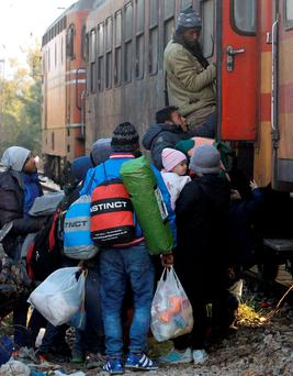 People rush to secure a place onboard a train heading towards Serbia at the transit center for refugees near the southern Macedonian town of Gevgelija, on Saturday, Nov. 7, 2015. (AP Photo/Boris Grdanoski)