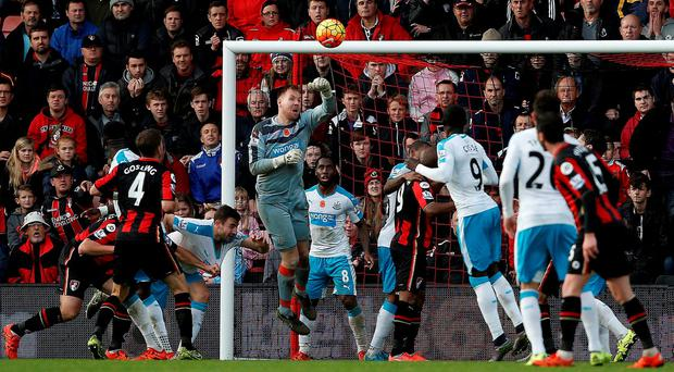 Rob Elliot (C) jumps to save an attempted shot from Bournemouth's English midfielder Dan Gosling