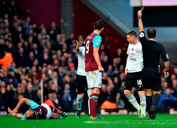 James McCarthy (2nd R) receives a yellow card from referee Paul Tierney for a foul on West Ham United's French midfielder Dimitri Payet