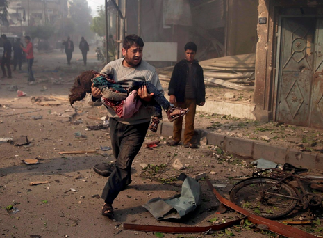 Carnage: A man carries an injured girl as he rushes away from a site hit by what activists said were airstrikes by forces loyal to Syria's President Bashar al-Assad, in the Douma neighborhood of Damascus Photo: Bassam Khabieh/Reuters