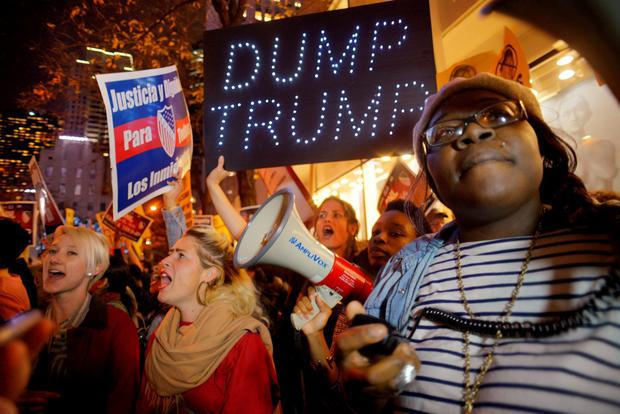 Sasha Murphy, of the ANSWER Coalition, leads demonstrators in a chant during a protest against Republican presidential candidate Donald Trump's hosting