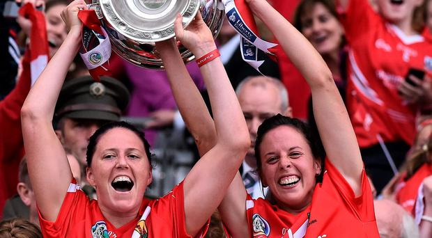 Cork players Gemma O'Connor, left, and Orla Cotter, lift the O'Duffy Cup