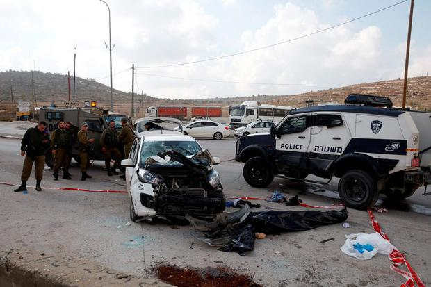 Israeli soldiers stand near a covered body (bottom R) on the scene of a car-ramming near the West Bank Jewish settlement of Tapuach south of Nablus November 8, 2015