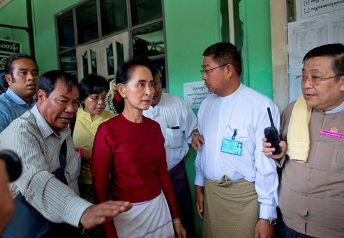 Myanmar's National League for Democracy party leader Aung San Suu Kyi, center, arrives at a polling station to vote in Yangon, Myanmar, Sunday, Nov. 8, 2015. Myanmar voted Sunday in historic elections that will test whether popular mandate can loosen the military's longstanding grip on power, even if opposition leader Suu Kyi's party secures a widely-expected victory