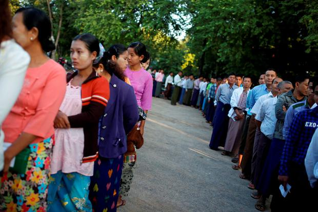 People stand outside a polling station in Mandalay, Myanmar, Sunday, Nov. 8, 2015. Myanmar voted Sunday in historic elections that will test whether popular mandate will help loosen the militarys longstanding hold on power even if opposition leader Aung San Suu Kyis party secures a widely-expected victory