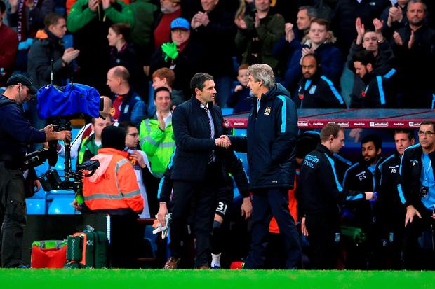 Manchester City manager Manuel Pellegrini and Aston Villa manager Remi Garde (centre left) shake hands after the final whistle