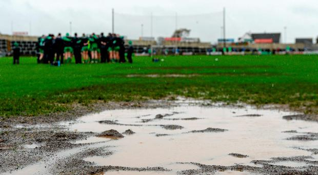 A view of the rain-soaked goalmouth in O'Moore Park yesterday as Sarsfields players gather for their team talk ahead of the clash with Portlaoise