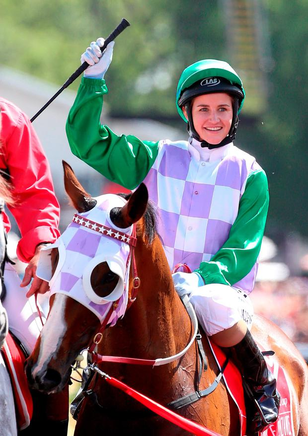 Michelle Payne acknowledges the crowds at Flemington Racecourse in Melbourne after her historic Melbourne Cup win on Prince of Penzance