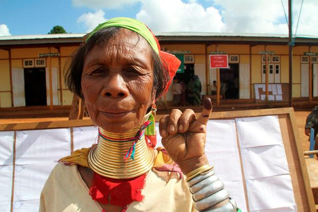 A Kayan woman, from one of Myanmar's ethnic minority groups, shows her ink-stained finger after she voted, in front of a polling station in Panpet Credit: Nay Lynn Thike